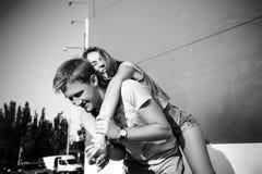 Любящий смеяться над пар черная девушка прячет белизну рубашки съемки s человека Стоковая Фотография