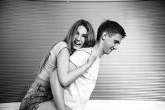 Любящий смеяться над пар черная девушка прячет белизну рубашки съемки s человека Стоковое фото RF