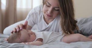 Любя мать со спать дочерью младенца на кровати сток-видео