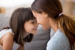 Любя молодая мама и меньшая дочь насладиться сладким моментом совместно стоковое изображение rf