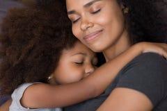 Любя одиночная черная мать обнимает милое соединение нежности чувства дочери стоковое изображение rf
