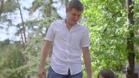 Любя отец помогает к его маленькой дочери пошатывать на качании в спортивной площадке в летнем дне, девушке усмехается сток-видео