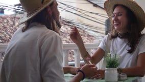 Любя пара в соломенных шляпах сидит на мороженом одина другого кафа и питания сток-видео