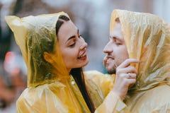 Любя пары, парень и его девушка одетые в желтых плащах обнимают на улице в дожде стоковая фотография