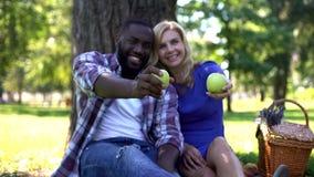 Любя пары показывая зеленые яблоки в камеру, выбирая здоровые продукты стоковые фото