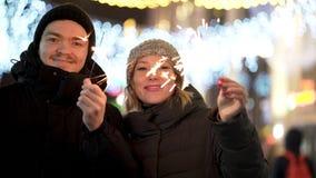 Любя пары с бенгальскими огнями усмехаться, смотря в глаза в городе зимы вечером, веселой концепции Christmass и Нового Года стоковые фотографии rf