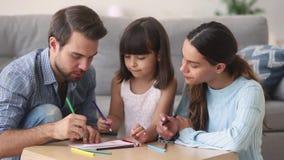 Любя родители рисуя с меньшей дочерью дома видеоматериал