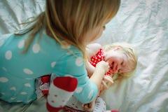 Любя старшая сестра щекоча младенца, детей играет дом, время семьи стоковые изображения