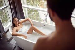 Любя человек и женщина ослабляя совместно в ванне стоковое изображение rf