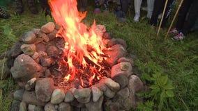 Люди бросают зерно в пламя камина сток-видео
