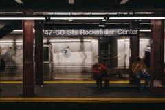 Люди внутри 47-50 Str метро центра Рокефеллер в Нью-Йорке, США, двигая поезде на предпосылке стоковое фото rf