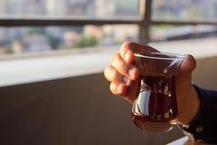 Люди вручают удержание традиционного турецкого стекла чая во время выпивать его стоковое изображение