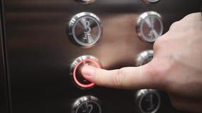 Люди вызывают лифт для того чтобы двинуть между полами видеоматериал
