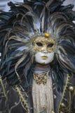 Люди в венецианском костюме масленицы в красочном костюме коричневых, черных и золота масленицы и маске Венеции Стоковое Фото