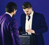 Люди в костюме или бизнесмены встречают для передачи черного портфеля Деловые партнеры с занятой стороной на голубой предпосылке Стоковое фото RF