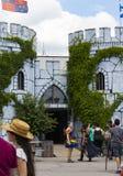 Люди в костюме собранном вокруг входа замка включая девушку одетую как фея радуги на фестивале Renassiance в m стоковые фотографии rf