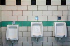 Люди в писсуарах комнаты туалета в здании для людей только, белые писсуары в men' bathroom s, белые керамические писсуары стоковые изображения