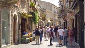 Люди в толпить солнечной улице популярного уютного маленького города Taormina в Сицилии видеоматериал