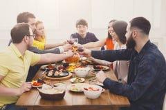 Люди говорят стекла clink приветственных восклицаний на праздничном официальныйе обед таблицы стоковые фото