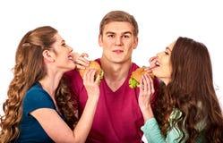 Люди группы едят гамбургер Женщины и фаст-фуд взятия человека стоковые фото