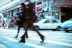 Люди двигая дальше crosswalk зебры на толпить город Hong Kong стоковые изображения rf