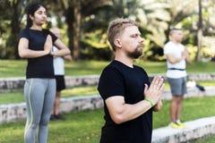 Люди делая йогу на парке Стоковые Изображения
