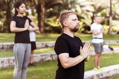 Люди делая йогу на парке Стоковые Фото