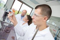 Люди делая медицинский эксперимент в лаборатории Стоковые Изображения