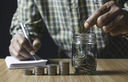 Люди документы Святого о деньгах спасения и положить монетку в стеклянный опарник на стол стоковое изображение rf