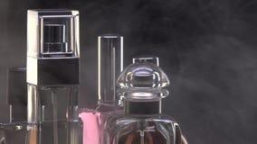 Люди, духи женщин в дыме, брызгах 5 бутылок во вращении сток-видео