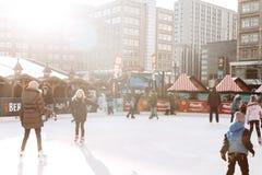 Люди едут на открытом катке на Alexanderplatz в Берлине стоковые фото