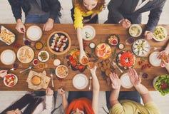 Люди едят здоровые еды и clink стекла на, который служат официальныйе обед таблицы Стоковые Фото