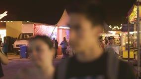 Люди есть парк атракционов помадок на городе ночи сток-видео