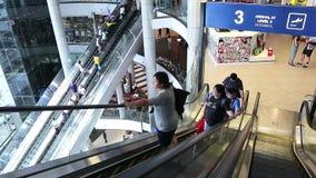 Люди ехать на эскалаторах в терминальном торговом центре на пересечении Asoke Montri, дороге Sukhumvit, Бангкоке, Таиланде сток-видео