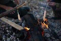 Люди жарят сосиски на открытом огне стоковое фото rf