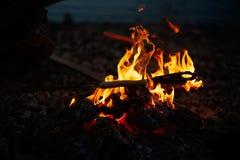 Люди жарят сосиски на открытом огне стоковые фотографии rf