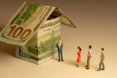 Люди ждут в очереди на фронте дома сделали из 100 долларовых банкнот Расходы недвижимости строя ипотеку и свойство стоковые изображения