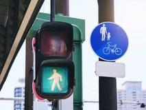 Люди зеленого света знака светофора пересекают майну велосипеда дороги пешеходную Стоковое фото RF