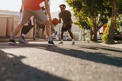 Люди играя баскетбол на улице Стоковое Фото