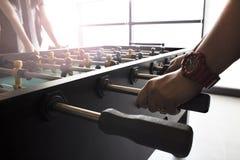 Люди играя наслаждающся чернотой и yel игры футбола таблицы Foosball стоковая фотография rf