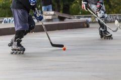 Люди играя хоккей улицы с ручками и роликами Стоковое Изображение RF