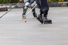 Люди играя хоккей улицы с ручками и роликами Стоковые Фото