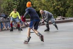 Люди играя хоккей улицы с ручками и роликами Стоковое фото RF