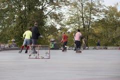 Люди играя хоккей улицы с ручками и роликами Стоковые Изображения