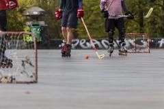 Люди играя хоккей улицы с ручками и роликами Стоковая Фотография
