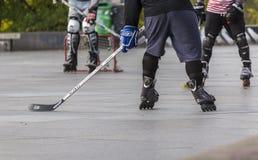 Люди играя хоккей улицы с ручками и роликами Стоковые Фотографии RF