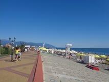 Люди идут вдоль прогулки взморья и ослабляют на пляжном комплексе Сочи, России Стоковые Фотографии RF