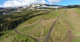 Люди идут вдоль пути в горах среди подъемов лыжи, воздушной стрельбы сток-видео