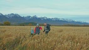 Люди идут около красивых гор в пшеничном поле перемещения семьи Окружающая среда людей горами Родители и ребенк сток-видео