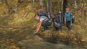 Люди идут около потока горы перемещения семьи Окружающая среда людей горами, реками, потоками Родители и малыши сток-видео